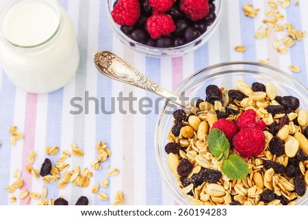 Honey glazed oatmeal, nut and coconut chips granola in a glass bowl with yogurt and fresh berries on a textile background - stock photo