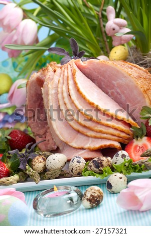Honey ham on Easter table with quail eggs, tulips and decoration - stock photo