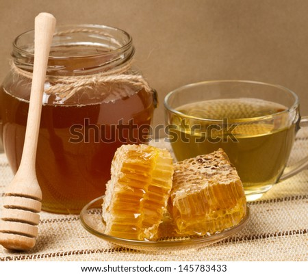 Honey, honeycomb and a cup of tea - stock photo