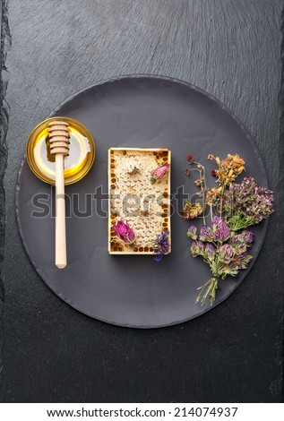 Honey, honeycomb and dried herbs  - stock photo