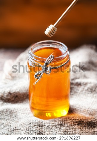 Honey in a glass jar with honey dipper on vintage wooden background close up.  - stock photo