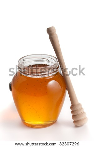 Honey in a glass jar with wooden spoon on side - stock photo