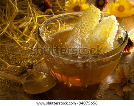Honey in a glass standing on the table among the flowers and straw - stock photo