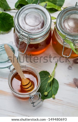 Honey in a jar and lime leaves - stock photo