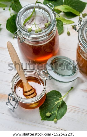 Honey in a jar and lime leaves on old wooden table - stock photo