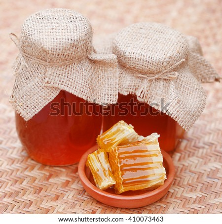 Honey in glass jar with bee hive on textured surface - stock photo