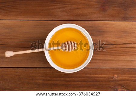 Honey in the jar with a spoon on a wooden table. Top view . - stock photo