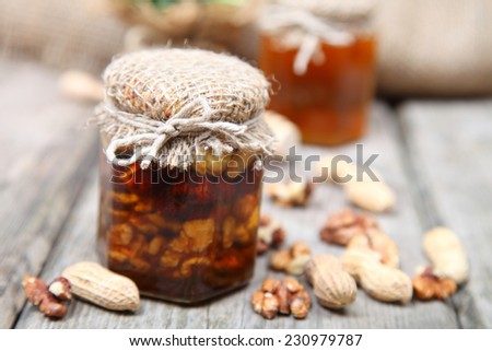 Honey in the pot and nuts on wooden background - stock photo
