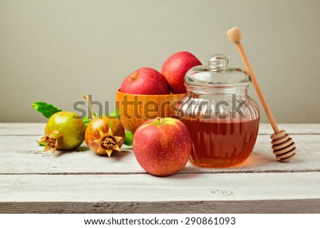 Honey jar and fresh apples with pomegranate on wooden board - stock photo
