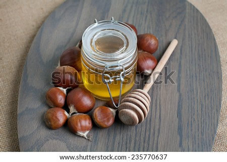 Honey jar with dripper and chestnuts - stock photo