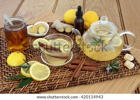 Honey, lemon, ginger and cinnamon drink for cold and flu relief with glass tea cup and pot, herbs, spices, medicine bottle, cough sweets and fresh fruit on wicker and bamboo mats over oak background. - stock photo