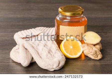 honey, lemon, ginger and mittens on black wooden background - stock photo