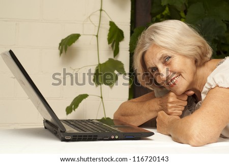 Honey older woman sitting at a table at home on the veranda - stock photo