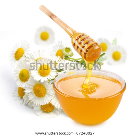 Honey pours with sticks in a jar. Flowers are near. Isolated on white background. - stock photo