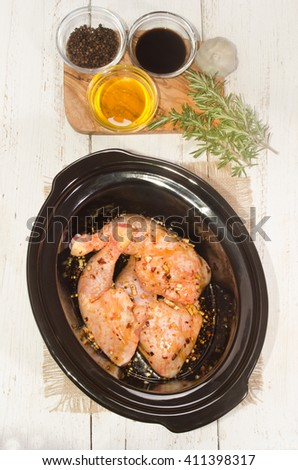 honey, soy sauce, garlic and black pepper marinated chicken leg in a crock pot - stock photo