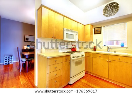 Honey tones kitchen room with white appliances. View of dining area - stock photo