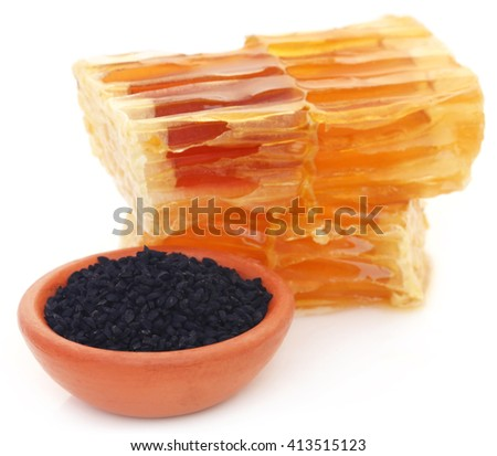 Honey with black cumin in a pottery over white background - stock photo