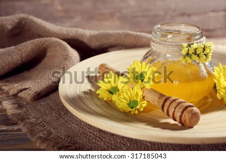 Honey with flowers and dipper on wooden tray on table - stock photo