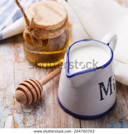 Honey with milk in the jug.selective focus - stock photo