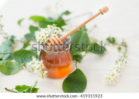 Honey with wooden honey dipper and glass jar and flowers. - stock photo