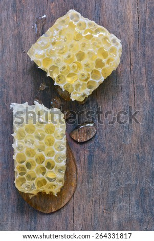 Honeycomb and honey drops over old wooden table - stock photo