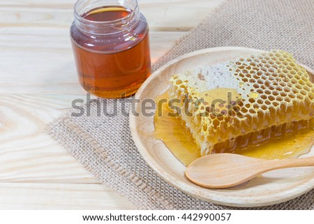 Honeycomb and wooden spoon in wood dish and jar with honey on jute cloth with wooden background. - stock photo