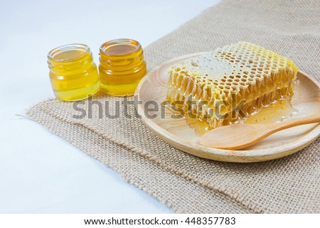 Honeycomb and wooden spoon in wood dish and small jars with honey on jute cloth with white background. - stock photo