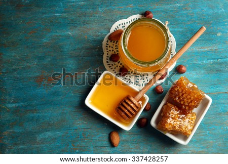 Honeycomb, glass pot with honey and nuts on color wooden background - stock photo