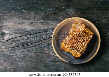 Honeycomb on ceramic plate over old wooden table. Top view. See series - stock photo