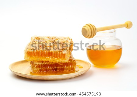 Honeycomb with jar and honey dipper isolated on white background - stock photo
