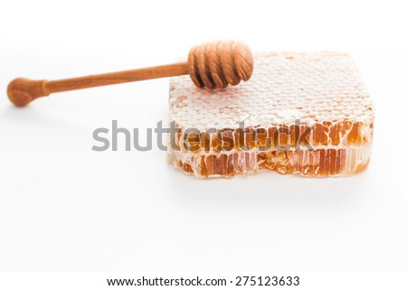 Honeycomb with wooden stick on a white background.  - stock photo