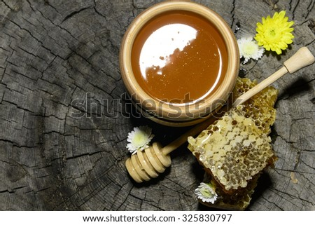 honeycombs and stick to honey on wooden background - stock photo
