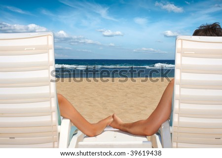 Honeymoon couple in beach chairs holding hands near ocean on reach resort - stock photo