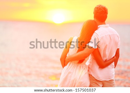 Honeymoon couple romantic in love at beach sunset. Newlywed happy young couple embracing enjoying ocean sunset during travel holidays vacation getaway. Interracial couple, Asian woman, Caucasian man. - stock photo
