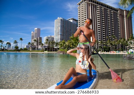 Honeymoon couple swimming in surfboard, tropical summer holiday vacation. Romantic couple joyful and full of happiness on travel vacation on Waikiki beach, Oahu, Hawaii, USA - stock photo