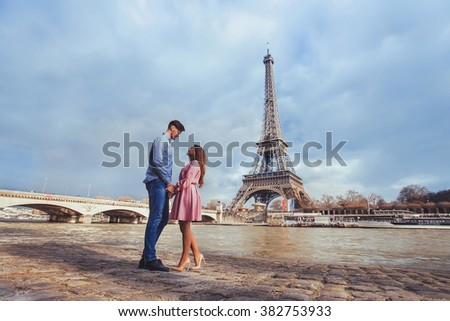 honeymoon in Paris, young beautiful couple on Eiffel Tower background - stock photo