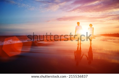 Honeymoon romantic couple in love walking on the beach on orange sunset background, happy young couple embracing enjoying ocean sunset during travel holidays vacation - stock photo