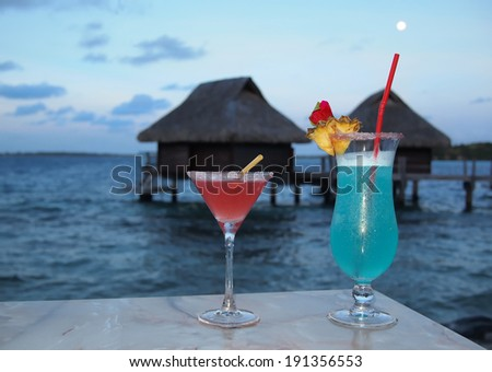 Honeymoon. Two cocktails on a table at dusk with in the background thatched overwater bungalows on the tropical island of Bora Bora near Tahiti in French Polynesia. - stock photo