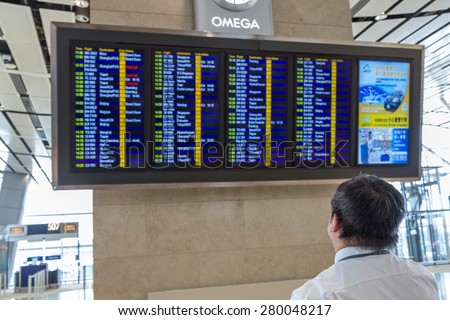 HONG KONG - APR 30, 2015: A person check the flight timetable in departure terminal of Hong Kong International Airport. About 90 airlines operate flights from HKIA to over 150 cities across globe. - stock photo