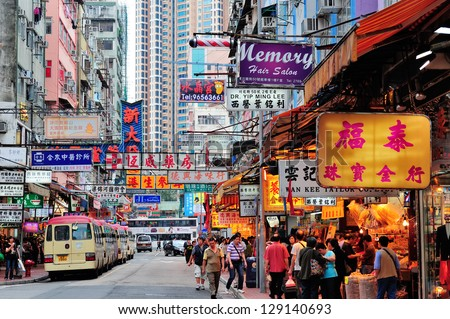 HONG KONG, CHINA - APR 23: Street view with traffic and shops on April 23, 2012 in Hong Kong, China. With 7M population and land mass of 1104 sq km, it is one of the most dense areas in the world. - stock photo