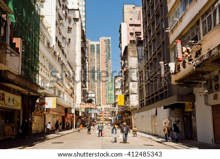 HONG KONG, CHINA - FEB 7: People on a street with tall scyscrapers with concrete walls in busy district of asian city on February 7, 2016. There are 1,223 skyscrapers in Hong Kong. - stock photo
