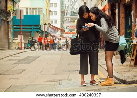 HONG KONG, CHINA - FEB 12: Two women watching cell phone to find way in big city on February 12, 2016. There are 1,223 skyscrapers in Hong Kong. - stock photo