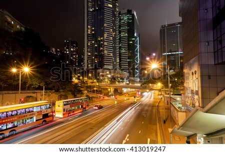 HONG KONG, CHINA - FEB 10: View of night city and motion lines on dark road with buses and urban structures on February 10, 2016. Hong Kong dollar is the eighth most traded currency in the world. - stock photo