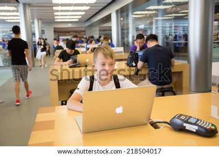 HONG KONG, CHINA - JUNE 15, 2014: Young shopper at Apple store in Hong Kong. Store is in a shopping center IFC Mall, it is very popular with locals and tourists visiting Hong Kong. - stock photo