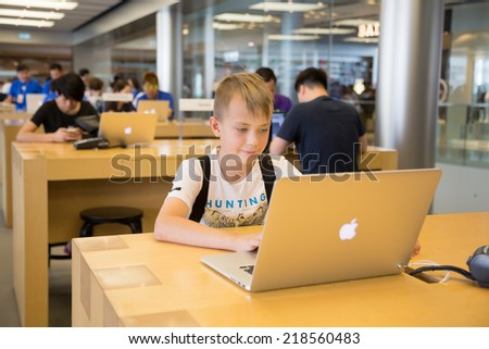 HONG KONG, CHINA - JUNE 15, 2014: Young visitor at Apple store in Hong Kong. Store is in a shopping center IFC Mall, it is very popular with locals and tourists visiting Hong Kong. - stock photo