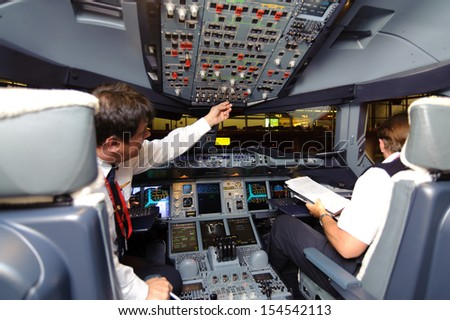 HONG KONG, CHINA - MAY 8, 2012: pilots in Emirates Airbus A380 aircraft after landing MAY 8, 2012. Emirates is the largest airline in the Middle East - stock photo