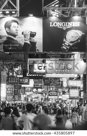 Hong Kong, China - October 03, 2015 : Many people in Mongkok street. Mongkok is characterized by a mixture of old and new buildings with shops and restaurants at street level. Monochrome photo,   - stock photo