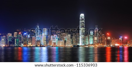 Hong Kong city skyline at night over Victoria Harbor with clear sky and urban skyscrapers. - stock photo