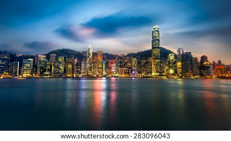 Hong kong city skyline at night over victoria harbor with clear sky and urban skyscrapers - stock photo
