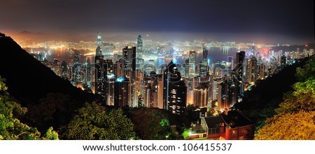 Hong Kong city skyline at night with Victoria Harbor and skyscrapers illuminated by lights over water viewed from mountain top. - stock photo
